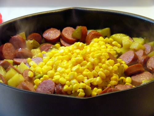 Add canned corn to the skillet with the sausage and potatoes.