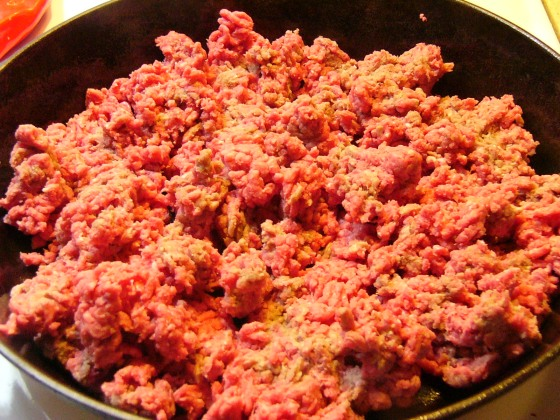 Brown ground beef in a large skillet over medium-high heat.
