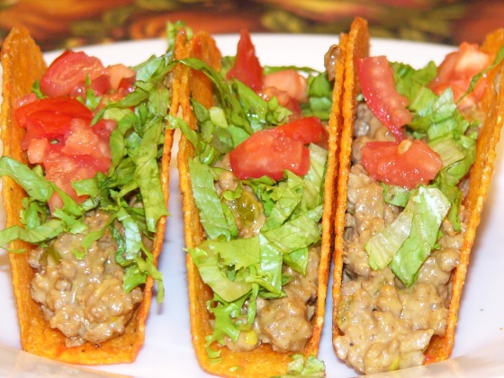 Fill taco shells with cheesy meat filling. Top with lettuce and tomatoes.