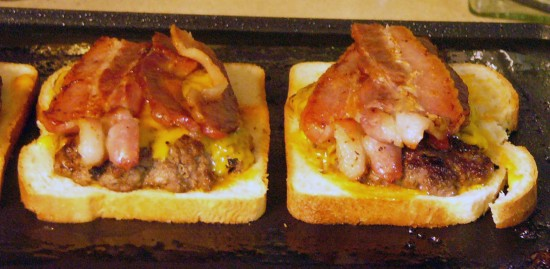 Place burgers on sourdough as it continues to grill. Place bacon strips on top of burgers.